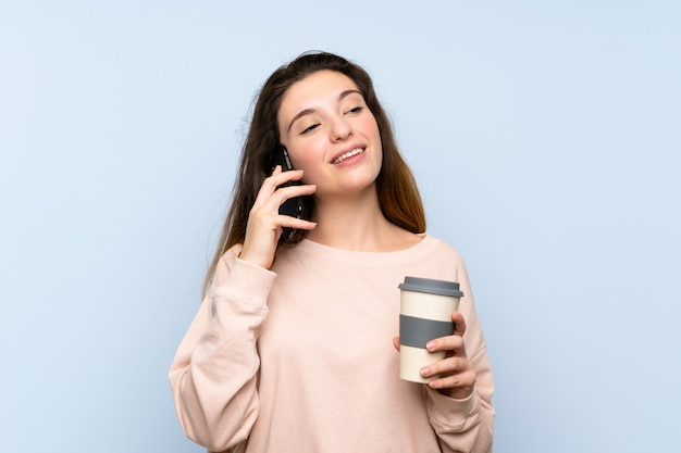 Young brunette girl holding coffee to take away and a mobile