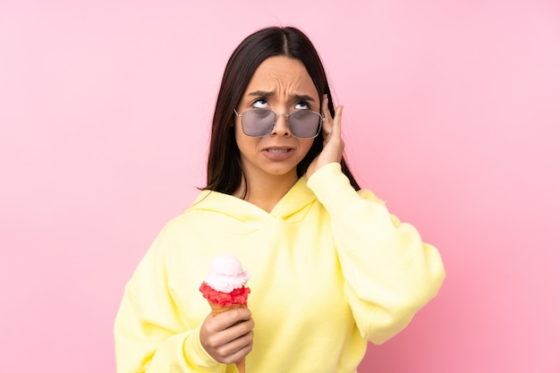Young brunette girl holding a cornet ice cream over isolated pink wall frustrated and covering ears