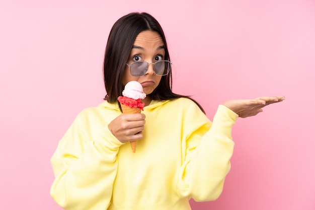 Young brunette girl holding a cornet ice cream over isolated pink wall making doubts gesture