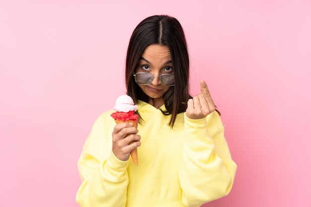 Young brunette girl holding a cornet ice cream over pink making money gesture