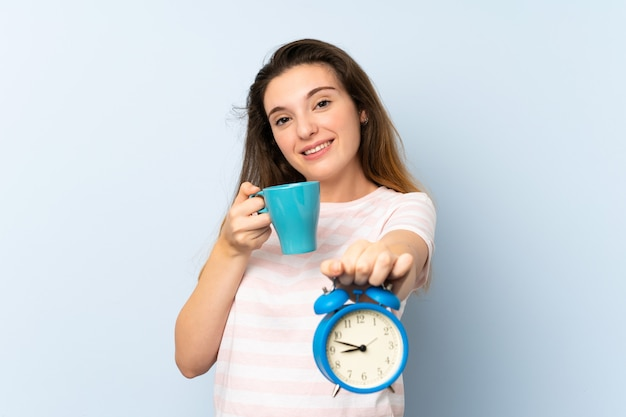 Young brunette girl holding a cup of coffee and vintage clock over isolated wall