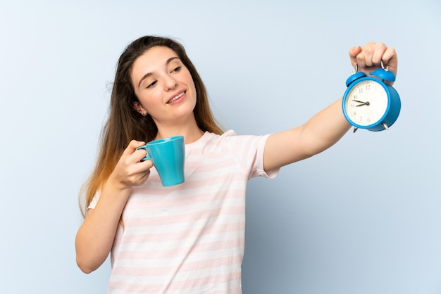 Young brunette girl holding a cup of coffee and vintage clock