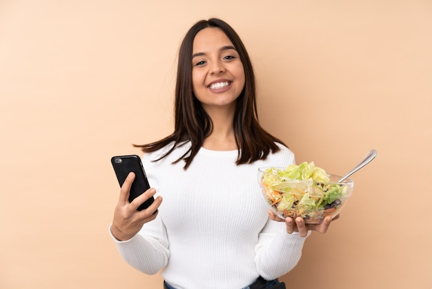 Young brunette girl holding a salad over isolated wall holding coffee to take away and a mobile