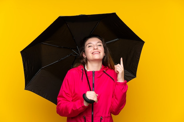 Young brunette girl holding an umbrella pointing up a great idea