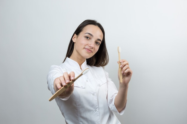 A young brunette girl holds an ecological toothbrush in her hands a girl in a white coat