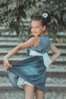 夏の公園で青いドレスを着た若いブルネットの少女。高品質の写真 Premium写真