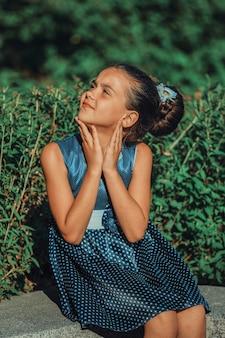 夏の公園で青いドレスを着た若いブルネットの少女。高品質の写真