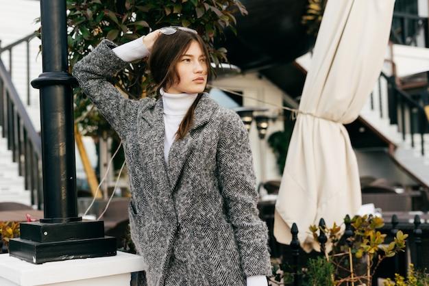 Молодая брюнетка в модном сером пальто гуляет по улицам города, наслаждаясь погодой