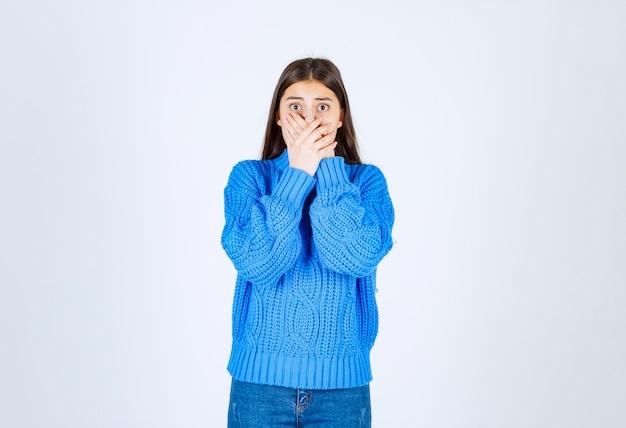 Молодая брюнетка девушка в синем свитере, оборачивая рот на белом.