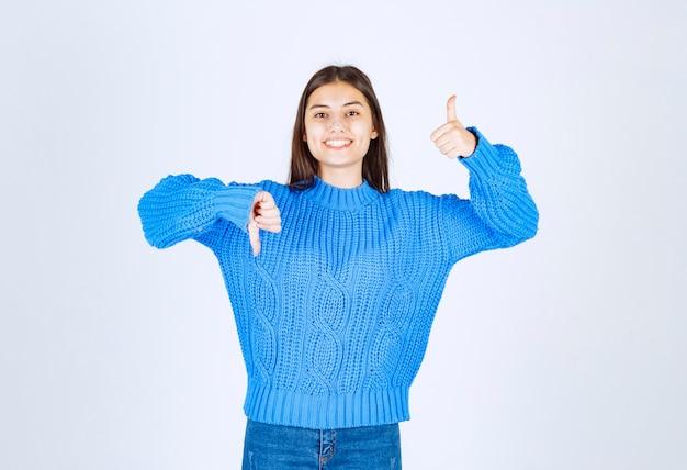 파란색 스웨터에 흰색 아래로 엄지 손가락을주는 젊은 갈색 머리 소녀.
