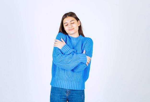 파란색 스웨터에 젊은 갈색 머리 여자는 흰색에 자신을 안 아. 무료 사진