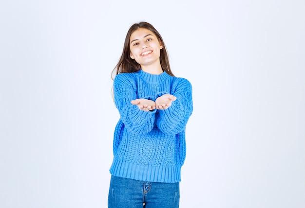 白を楽しみにして青いセーターの若いブルネットの女の子。