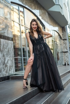 ガラスの建物の前の近くでポーズをとってエレガントな黒のイブニングドレスの若いブルネットの少女