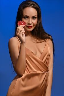 실크 황금 드레스에 젊은 갈색 머리 소녀 그녀는 파란색 벽에 포즈 두 개의 빨간 칩을 보여주는 미소