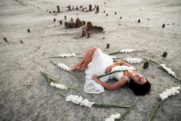 Молодая брюнетка в белом платье с закрытыми глазами лежит на берегу моря в окружении белых гладиолусов
