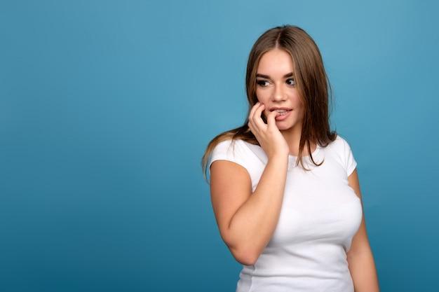 何か、青い背景の誘惑されないようにしようとしている白いtシャツの若いブルネットの少女