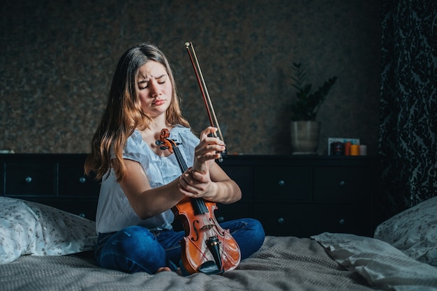 A young brunette girl injured her wrist while playing the violin. a girl sits on a bed in her room and holds a sore wrist with her hand.