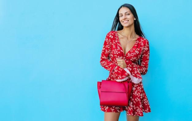 若いブルネットの少女は、赤いドレスを着て青い背景にポーズをとって、赤いハンドバッグを持って、笑顔で左を見て