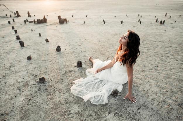 Молодая брюнетка сидит на песке с закрытыми глазами, одетая в белое повседневное платье
