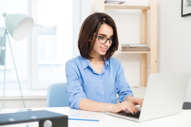 A young brunette girl is typing on laptop  at the table in office. she wears blue shirt and black glasses. she looks satisfied with her work.