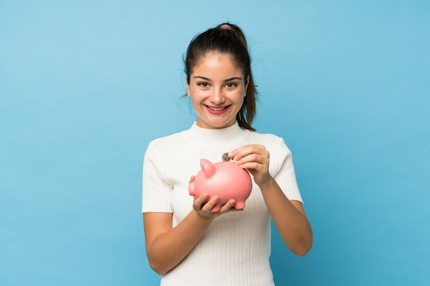 Young brunette girl over isolated blue holding a big piggybank