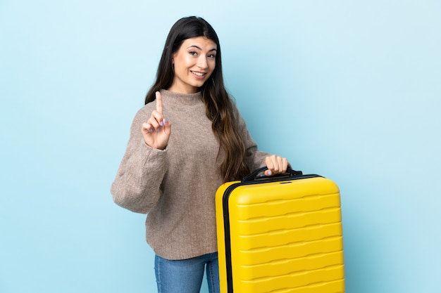 Young brunette girl over isolated blue in vacation with travel suitcase and counting one