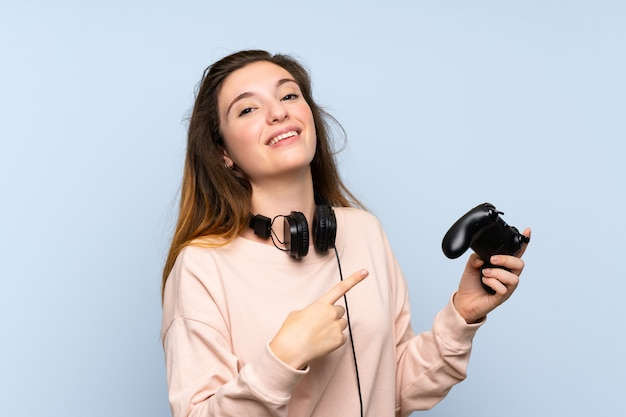 Young brunette girl over isolated blue wall playing at videogames