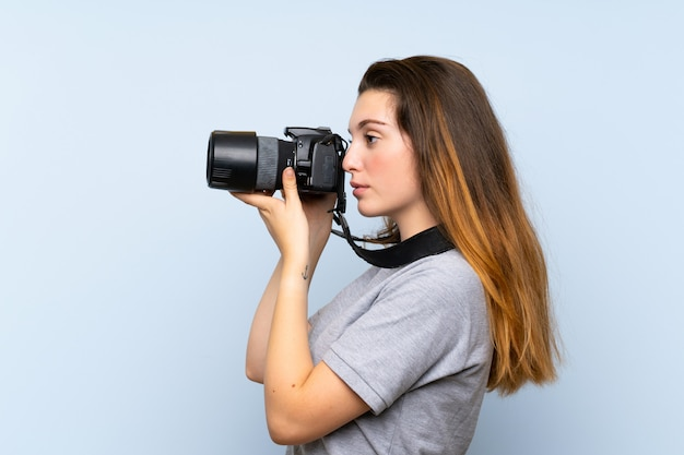 Young brunette girl over isolated blue wall with a professional camera