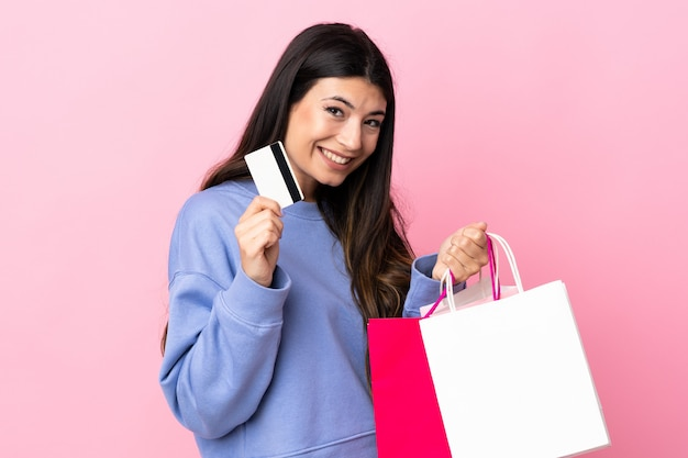 Young brunette girl over isolated pink wall holding shopping bags and a credit card