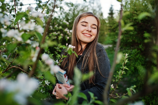 Young brunette girl at jeans against spring blossom tree with book.