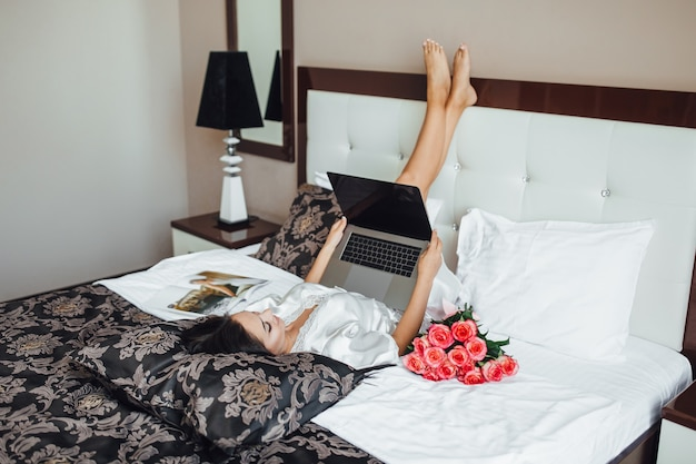 Young brunette girl lays on her bed, in the morning and holds a laptop. beautiful roses near her. top view.