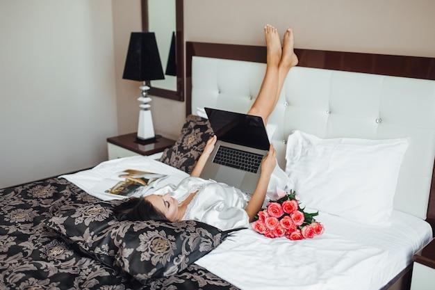 젊은 갈색 머리 소녀는 아침에 그녀의 침대에 낳고 노트북을 보유하고 있습니다. 그녀 근처의 아름다운 장미들. 평면도.