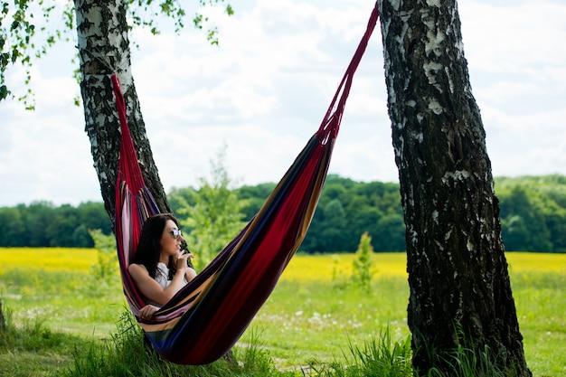 Молодая брюнетка девушка лежит в гамаке и разговаривает по мобильному телефону.