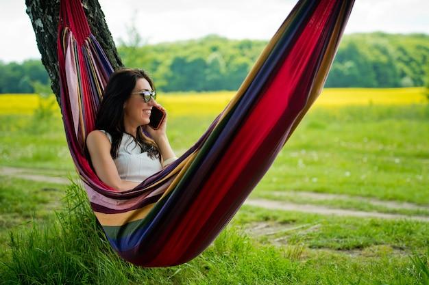 若いブルネットの少女はハンモックに横たわって携帯電話で話します。