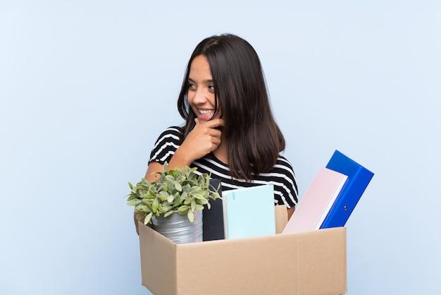 Молодая брюнетка девушка делает ход, поднимая коробку с вещами, думая, идея и глядя в сторону