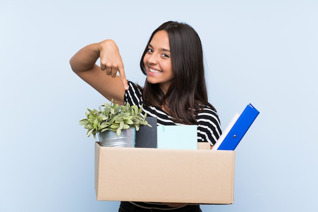 Young brunette girl making a move while picking up a box full of things and pointing it