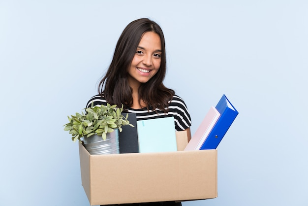 Young brunette girl making a move while picking up a box full of things smiling a lot