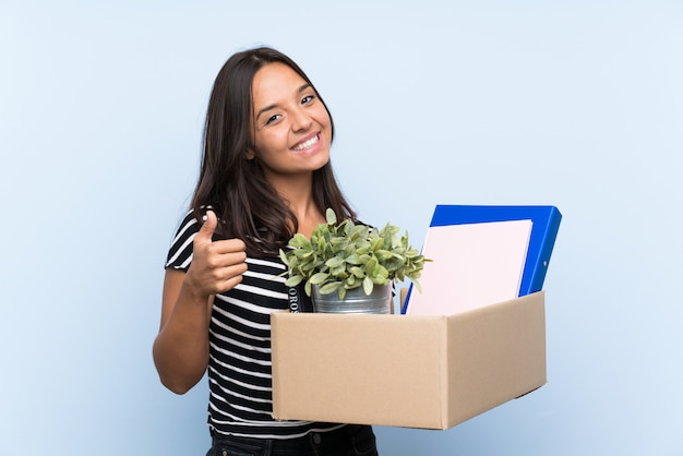 Young brunette girl making a move while picking up a box full of things with thumb up