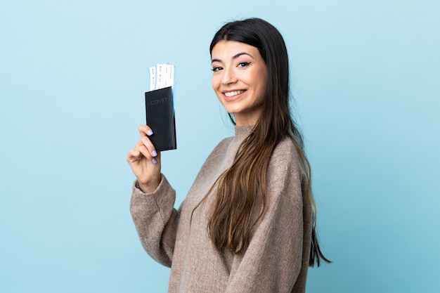 Молодая брюнетка девушка над синей стеной счастливы в отпуске с паспортом и билетами на самолет