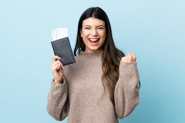 Молодая девушка брюнет над изолированным голубым счастливым в каникулах с паспортом и билетами на самолет