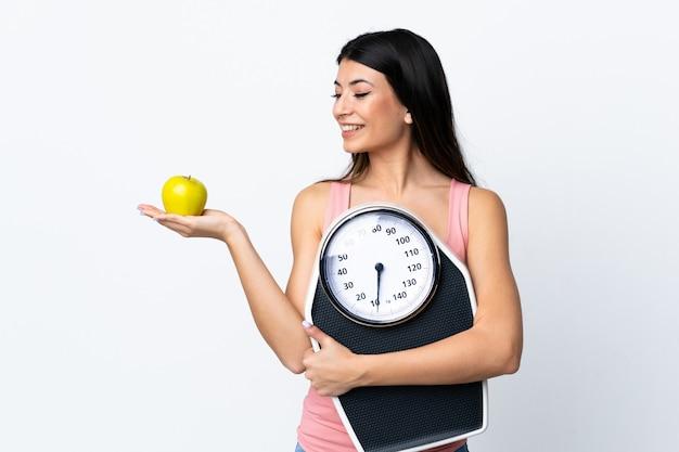 사과를 보면서 무게 기계를 들고 고립 된 흰색 위에 젊은 갈색 머리 소녀