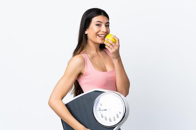 Молодая брюнетка девушка над изолированной белой стеной с весами и с яблоком