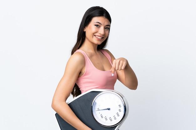 무게 기계를 들고 그것을 가리키는 흰 벽에 젊은 갈색 머리 여자