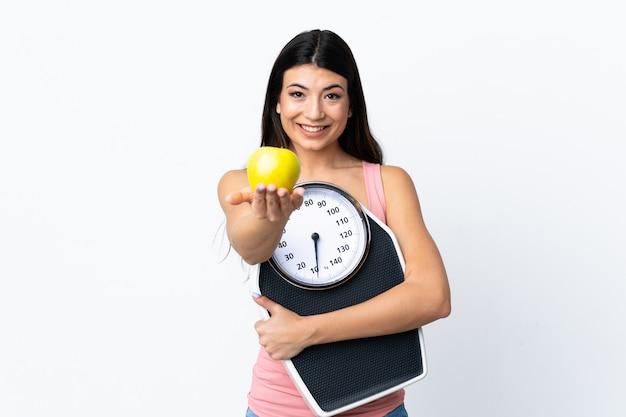 Молодая брюнетка девушка над белой стеной держит весы и предлагает яблоко
