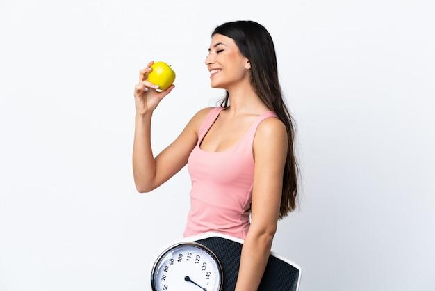 Молодая брюнетка на белой стене с весами и яблоком