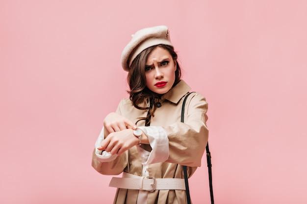 젊은 갈색 머리 여자는 그녀의 손목 시계를 가리 킵니다. 베레모와 트렌치 코트를 입은 여성이 비난하면서 카메라를 바라 봅니다.