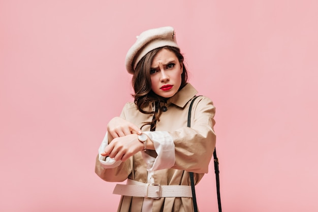 Young brunette girl points at her wrist watch. woman in beret and trench coat reproachfully looks into camera.