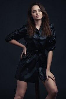 Молодая брюнетка девушка позирует в стильной одежде