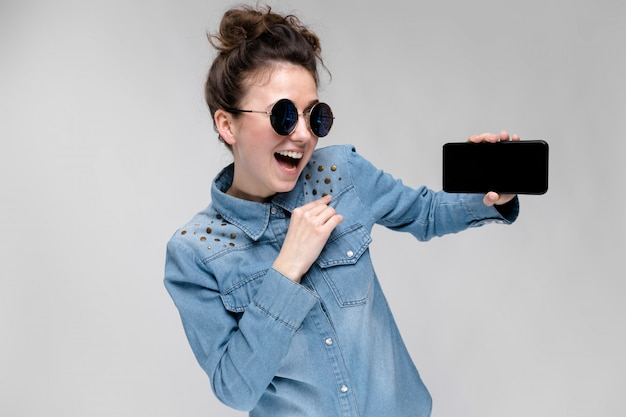 Young brunette girl in round glasses. hairs are gathered in a bun. girl with a black phone.