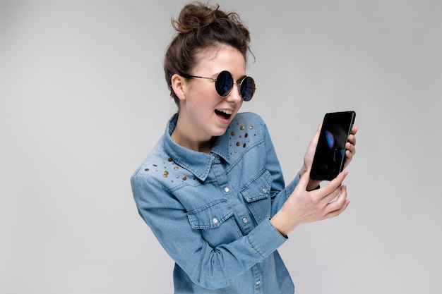 Young brunette girl in round glasses with a black phone